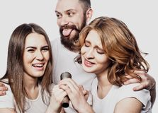Group of friends playing karaoke over white background. Concept about friendship and people. Studio shoot Royalty Free Stock Photography