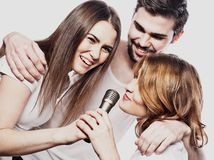 Group of friends playing karaoke over white background. Concept about friendship and people. Studio shoot Stock Images