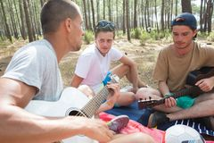 Group friends playing music in woods Stock Photos
