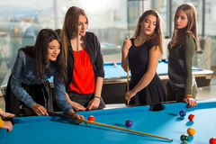 Group of friends playing pool together. Royalty Free Stock Images