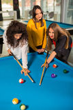 Group of friends playing pool together. Stock Image