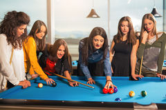 Group of friends playing pool together. Royalty Free Stock Image