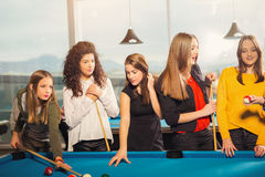 Group of friends playing pool together. Royalty Free Stock Photo