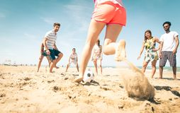 Group of friends playing soccer on the beach. A girl is shooting to score a goal. concept about friends, sport, vacations and people Royalty Free Stock Photos