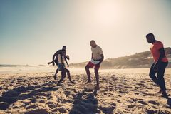 Group of friends playing soccer on the beach. Group of friends having fun on the beach playing football. Young people playing soccer on sandy beach Royalty Free Stock Photos