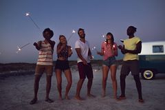 Group of friends playing with sparklers on the beach at dusk. Front view of happy group of diverse friends playing with sparklers on the beach at dusk royalty free stock images