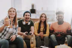 Group of friends playing video games and enjoying drinks at home royalty free stock photos
