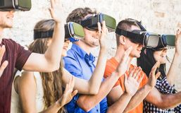 Group of friends playing on virtual reality vr goggles. Group of friends playing on vr goggles outdoors - Virtual augmented reality and wearable tech concept stock photo
