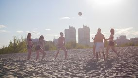 A group of friends playing volleyball on the beach against a beautiful sunset stock photography