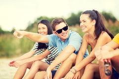 Group of friends pointing somewhere on the beach. Summer, holidays, vacation, happy people concept - group of friends pointing somewhere on the beach Royalty Free Stock Photography