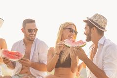 Friends eating watermelon stock images