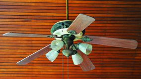 Vintage classic old ceiling electric fan. Vintage classic old ceiling electric fan with teak wood panel background royalty free stock photography