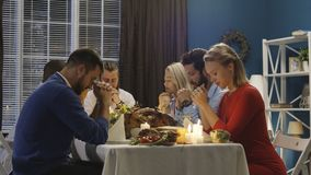 Group of friends praying on Thanksgiving day celebration. Men and women giving worship before starting delicious meal at table having Thanksgiving holiday royalty free stock photography