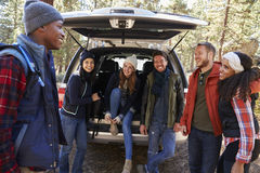 Group of friends prepare for a hike at the open back of car Royalty Free Stock Photos