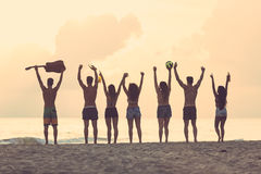 Group of friends raising hands on the beach at sunset royalty free stock image