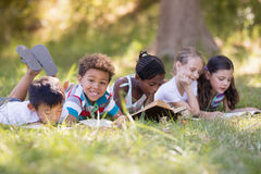 Group of friends reading book at campsite. Group of friends reading book on grassy field at campsite stock photography