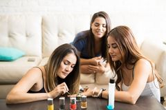 Girls talking and putting nail polish on. Group of friends relaxing at home and putting some nail polish on to each other Stock Photo