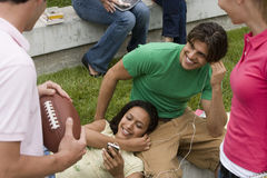 Group of friends relaxing outdoors, couple listening to MP3 player, man holding american football Stock Photos