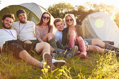 Group Of Friends Relaxing Outside Tents On Camping Holiday Stock Photo