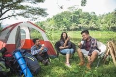 Friends Relaxing Outside Tents On Camping. Group of Friends Relaxing Outside Tents On Camping Holiday Royalty Free Stock Photography