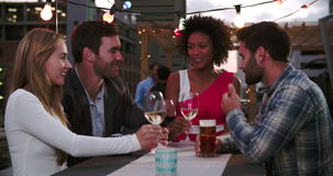 Group Of Friends Relaxing Together At Rooftop Bar. Group of friends enjoying drinks and talking at rooftop bar.Shot in 4k on Sony FS700 at frame rate of 25fps stock video footage