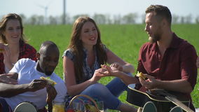 A group of friends rest on a picnic and eat sandwiches, slow-motion shooting stock footage
