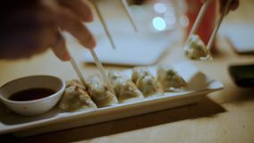 Friends share food at restaurant, eat gyozas. Group of friends in restaurant or cafe have funa dn enjoy delicious exotic food at tapas bar, asian dumplings or stock video footage