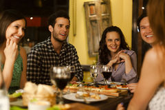 Group of friends in a restaurant. Group of young adult friends talking in a restaurant at night Stock Photos