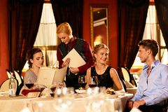 Group of friends in restaurant. Group of young friends with menus choosing in a luxury restaurant royalty free stock image