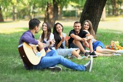 Group of friends resting in park on sunny day. Guy playing the guitar and three young women and one men listening to the song and smiling. People having fun in Stock Photo