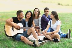 Group of friends resting in park on sunny day. Guy playing the guitar and three young women and one men listening to the song and smiling. People having fun in Royalty Free Stock Photos