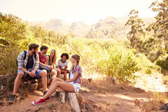 Group Of Friends Resting On Walk Through Countryside Royalty Free Stock Images
