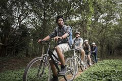 Group of friends ride mountain bike in the forest together Royalty Free Stock Photos