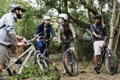 Group of friends ride mountain bike in the forest together Stock Photography