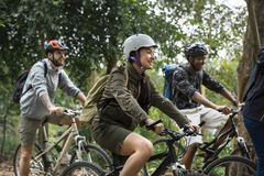 Group of friends ride mountain bike in the forest together Stock Photos