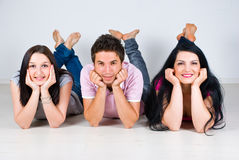 Group of friends in a row lying  on floor Stock Images
