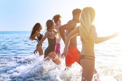 Group of friends run in the sea. Concept of summertime royalty free stock image