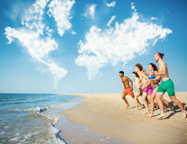 Group of friends run in the sea with world map made of clouds. Concept of summertime. Group of friends run in the blue sea with world map made of clouds. Concept Royalty Free Stock Photography