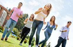 Group of friends running Stock Image