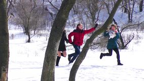 A group of friends are running in the snow. slow motion stock video footage