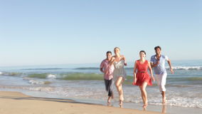Group Of Friends Running Up Beach Towards Camera Royalty Free Stock Images