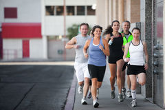 Group of friends runs downtown. Royalty Free Stock Image