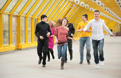 Group of friends runs on footbridge Royalty Free Stock Photos