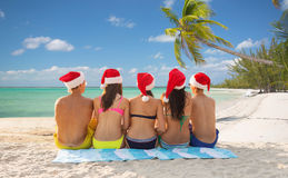 Group of friends in santa helper hats on beach Royalty Free Stock Photography