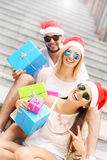 Group of friends in Santa's hats with presents Royalty Free Stock Images