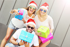 Group of friends in Santa's hats with presents Stock Photos