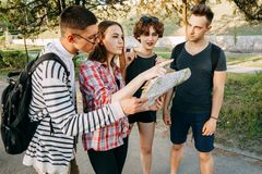 Group of friends searching location on city map. Traveling, sightseeing, group travel, city tour, student exchange program, togetherness. Group of friends Stock Photos