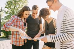 Group of friends searching location on city map. Traveling, sightseeing, group travel, city tour, student exchange program, togetherness. Group of friends Royalty Free Stock Photo