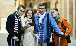 Group of friends shooting mutual portrait on cell phone. Group of happy european friends shooting mutual portrait on cell phone outdoors Royalty Free Stock Images