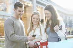 Group Of Friends Shopping In Mall Looking At Mobile Phone Stock Image